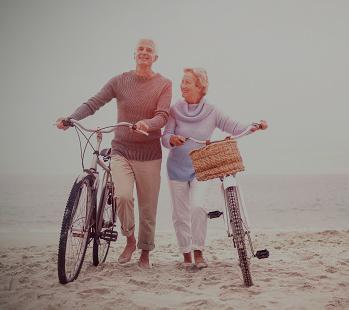 Ouder echtpaar op strand met Fiets verzekeringen Spanje