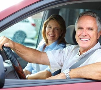 2 ouder mensen achter het stuur van een rode auto dankzij Nederlandse verzekeringskantoor aan de Costa Blanca